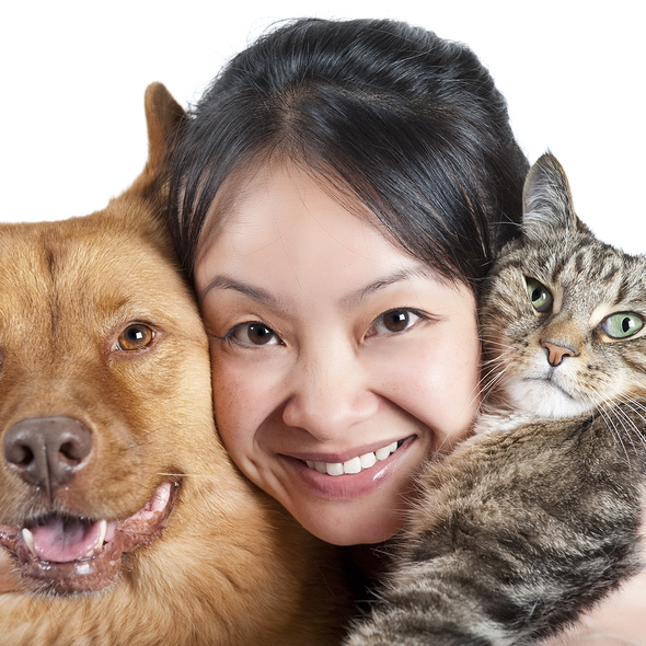Woman hugging her dog and cat